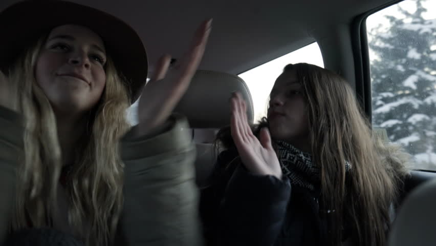Excited Teen Girls Clap In Unison And Sing Along To Favorite Song In Backseat Of Car