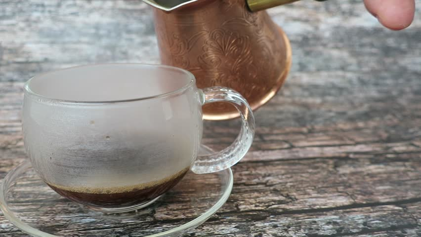 Pouring coffee from cezve into the glass cup