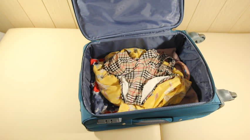 Young Woman Puts Tickets In The Suitcase And Closes The Zipper. 2 Shots happy young woman packing her personal belongings in bright green suitcase. puts clothes on vacation. | Shutterstock HD Video #23833585