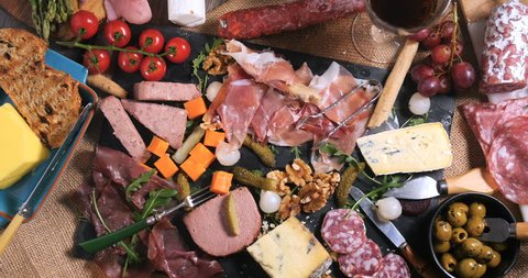 Dolly bird eye view of a platter of cured meat (charcuterie), ham, salami, pate and cheese