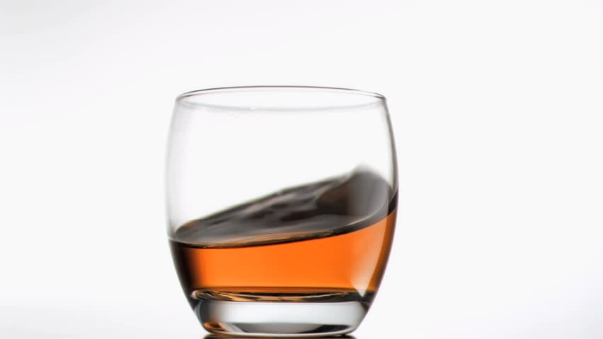 Whiskey turning in super slow motion in a glass against a white background