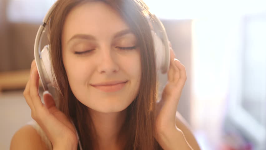 Portrait of young attractive girl in urban background listening to music with headphones 4k 20s