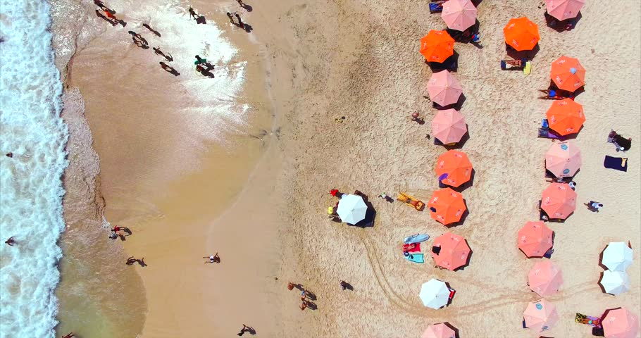 Dreamland beach from aerial top view. Tourists relaxing and surfing, umbrellas and deck chairs on the beach. Famous balinese beach. Bali, Indonesia