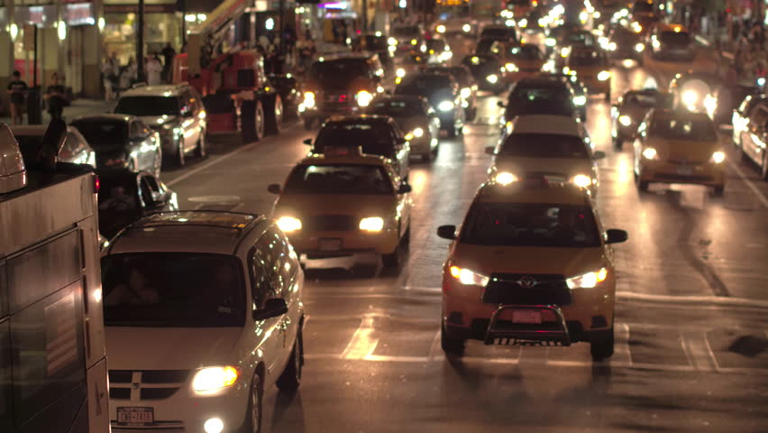 NEW YORK, USA - SEPTEMBER 23rd 2016: Cars, yellow cabs, SUVs and semi trucks queued in rows, driving along busy road during rush hour at night. Congestion on local street in New York City downtown