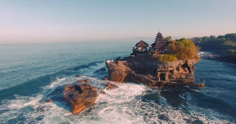Tanah Lot Temple on the rock in Sea. Ancient hinduism place of worship. Sunlight. Aerial view. Bali, Indonesia