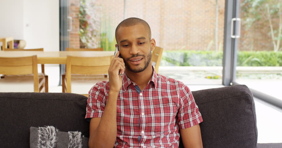4k, Attractive African American man talking on his mobile phone from home. Slow motion. | Shutterstock HD Video #23905195