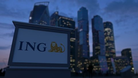 Street signage board with ING Group logo in the evening.  Blurred business district skyscrapers background. Editorial 3D rendering 4K