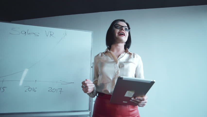 Young businesswoman wearing glasses giving a presentation with a tablet pc in her hand pointing towards a chart on a white board display during a meeting or conference. | Shutterstock HD Video #23929825