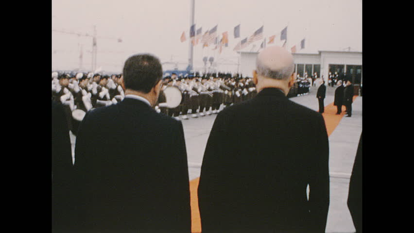 UNITED STATES 1960s: Military band playing, Richard Nixon with Charles de Gaulle / Handheld camera, tracking shot of band / Tracking shot of band, officials walk up stairs.