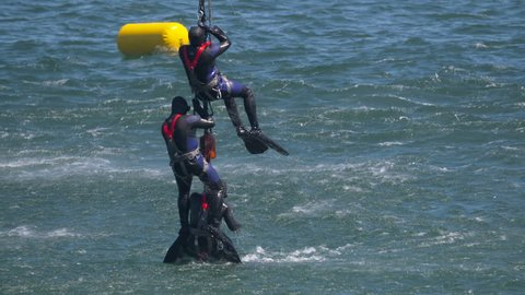 Stealthily navy seals leave the water with weapons drawn