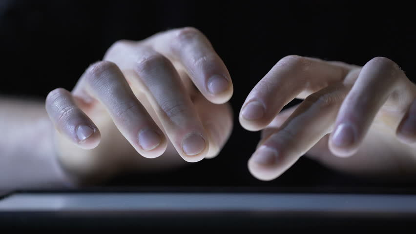 Hands of male web designer sliding and zooming pictures on modern tablet pc