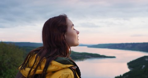 Close up of beautiful young woman looking up at sky out towards horizon view on top of mountain enjoying mindfulness spiritual moment in nature