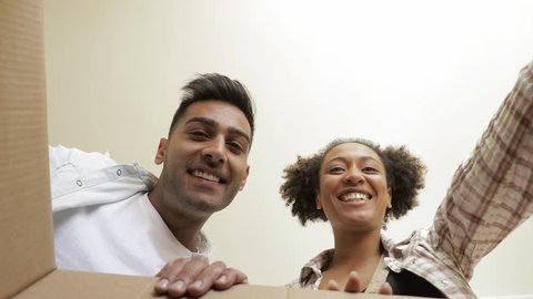 Happy couple looking inside the box POV