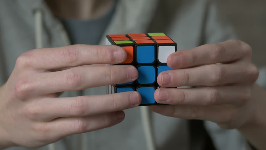 Boys hands solving rubik cube and showing thumb.   Shutterstock HD Video #24126658