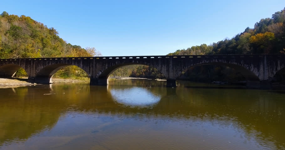 Cinematic shot of an old stone bridge crossing a calm Cumberland River as the camera travels upstream & under the middle arch on a day with a clear blue sky & fall leaves on the trees in mid Autumn.