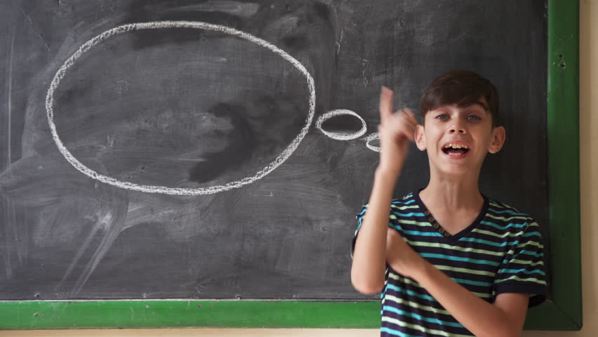 Concepts on blackboard at school. Young people, students and pupils in classroom. Intelligent and smart hispanic boy in class. Portrait of male kid smiling, having good idea  | Shutterstock HD Video #24132565
