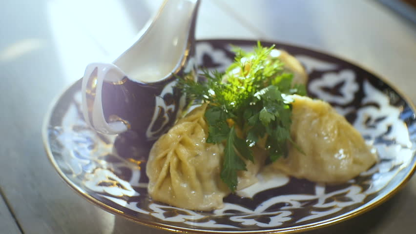 macro person cuts Tatar patty manty dumplings with knife fork on blue and white plate with sauce-boat on white table