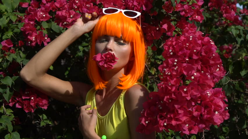 Closeup of woman posing with flower in her mouth during summer day over red flowers background. Creative look of woman wearing yellow swimsuit, orange wig and white sunglasses - slow motion video