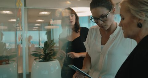 Business women having a meeting in modern office, standing in front of glass wall with post it notes, using digital tablet.