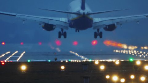 Commercial Jet Airplane Landing in airport runway at dusk, early night.
