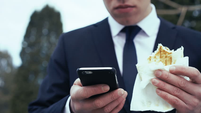 Energy bisnesmen decides on the phone and eats fast food. 4k | Shutterstock HD Video #24204145