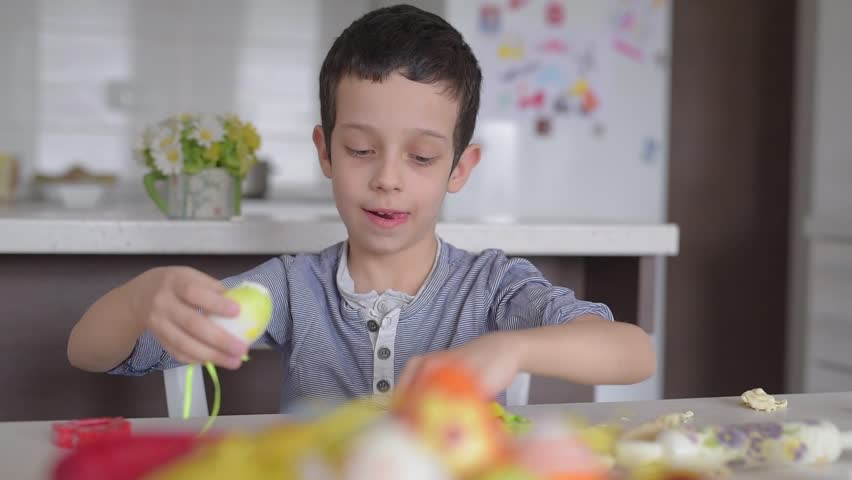 Young boy playing with dough and Easter eggs at home | Shutterstock HD Video #24206452