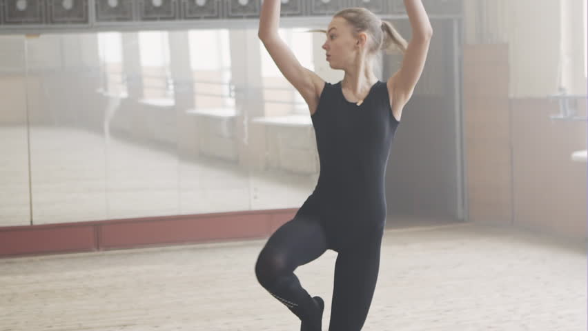 Ballet dancers warming in a studio with mirrors. Classical ballet class. Ballerina`s training, steps, and position. Slow motion.