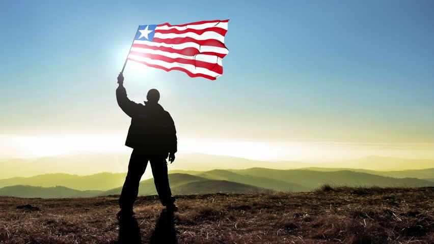 Successful silhouette man winner waving Liberia flag on top of the mountain peak, Cinemagraph LOOP background #24223015