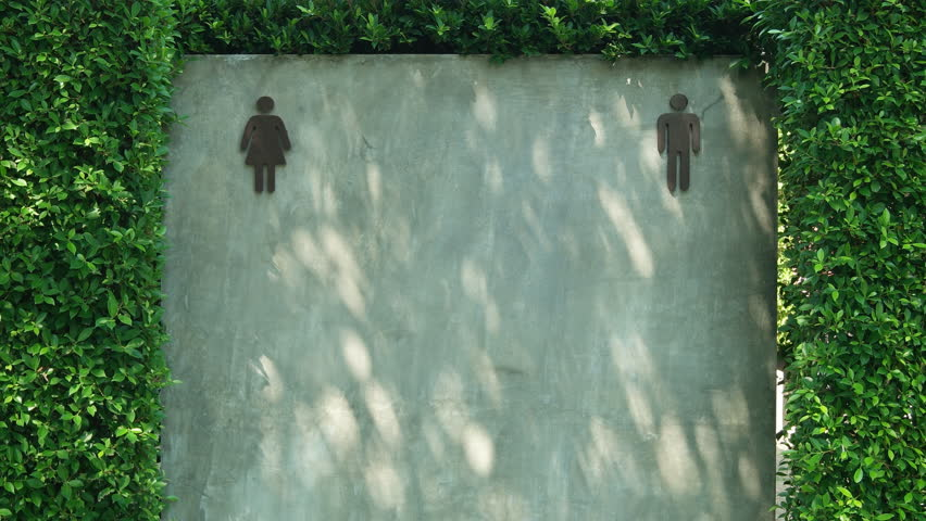 A unisex public toilet sign is on a grey cement wall and green leaf.