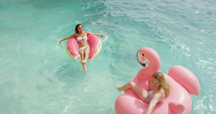 Two girls lying on inflatable flamingo Best friends having fun relaxing floating clear blue ocean Happy Women enjoying summer vacation tropical island beautiful beach bodies wearing bikini  TOP VIEW