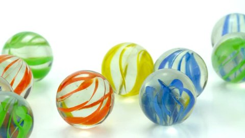 Rolling colorful glass marbles on white background