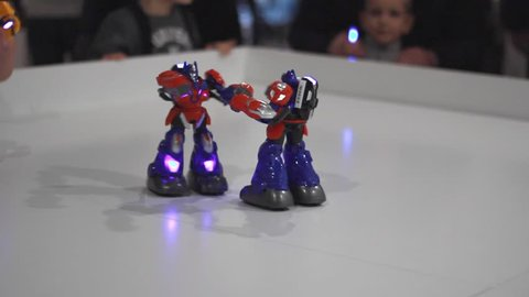 Robot fight on white ring. Toy robots fighting. Robot wars kids toys. Two transformer robots boxing. Robotic technology game. Battle robot game