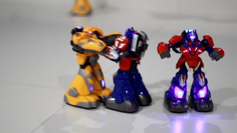 Robots fighting show. Closeup of remote control toy robots fighting. Close up of fighting robots on white floor. Transformer robot boxing. Toy robots fight. Battle robotic toy