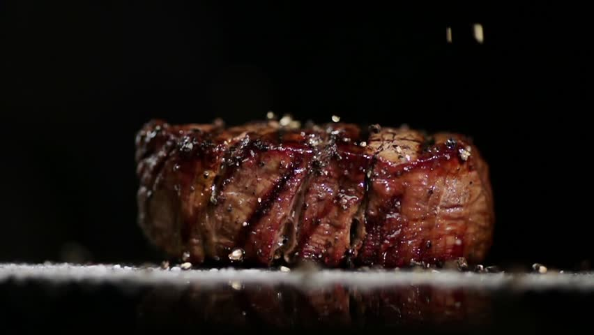 SLOW MOTION FOOD: large grains of pepper fall on juicy grilled filet mignon close up
