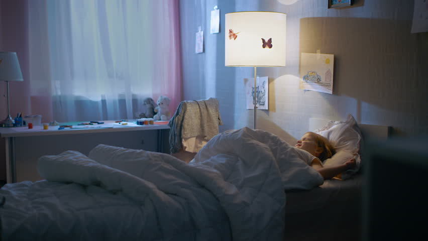 Young Loving Mother Tucks in Her Cute Little Daughter and Turns Off the Light. Shot on RED EPIC-W 8K Helium Cinema Camera.