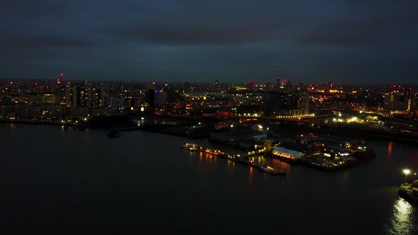 Aerial footage of the lighthouse at Trinity Buoy Wharf at night (4K)