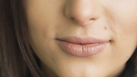 Extreme close up of woman licking and bitting lips. Slowly