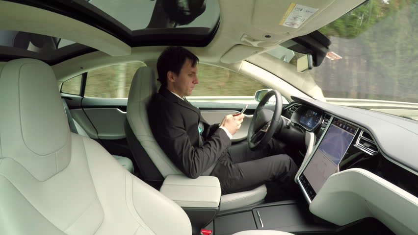 CLOSE UP: Young businessman texting writing messages on mobile phone while sitting behind self-driving steering wheel in autonomous autopilot driverless electric car traveling along countryside road | Shutterstock HD Video #24320456