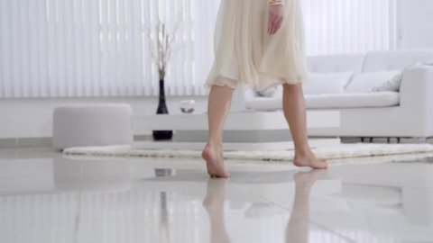 Beautiful young girl bare feet moving on interior in the living room in slow motion. View of young girl elegantly to walk.Sexy legs. Floor. Gait. Slow motion family home part 6 of 15.