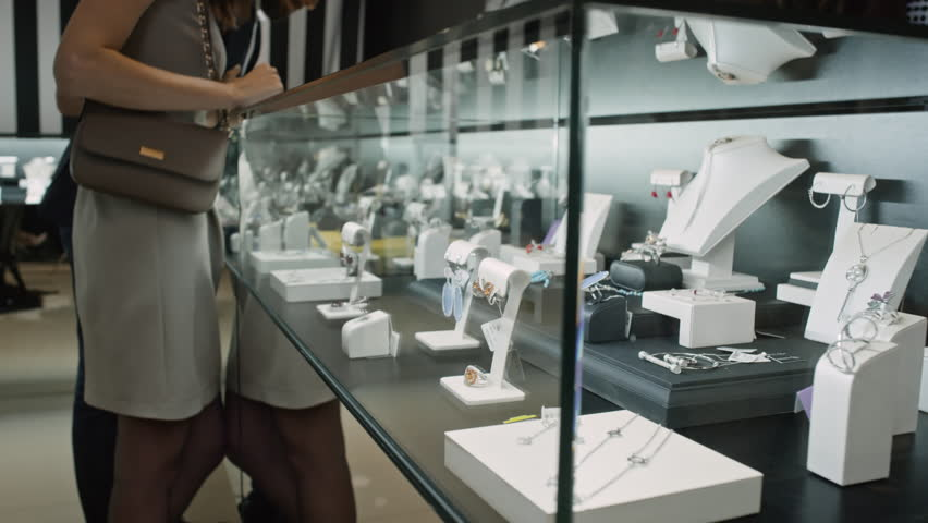 Couple of customers standing at glass display in jewelry boutique and looking at variety of precious pieces   Shutterstock HD Video #24353357