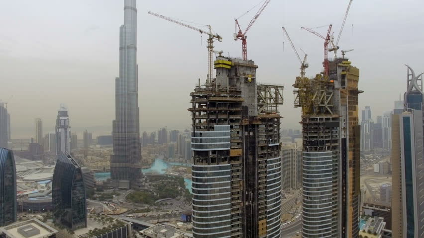 aerial view of several skyscrapers under construction with scaffolding and cranes. Dubai, UAE