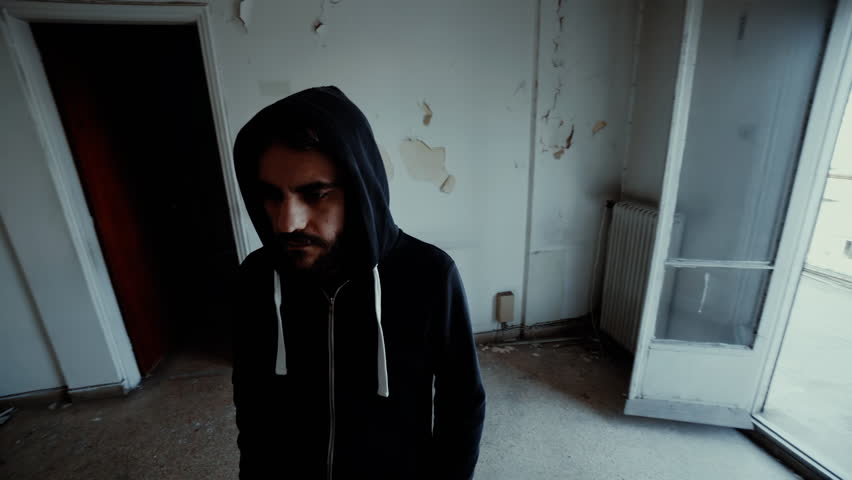Hooded depressed young man in empty abandoned house.A young man wearing a hoodie inside a derelict destroyed apartment in the city | Shutterstock HD Video #24364925