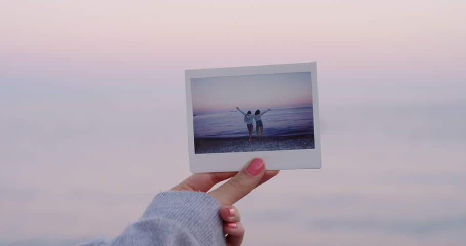 Close up hand holding polaroid photograph in front of beautiful tropical beach sunset travel concept
