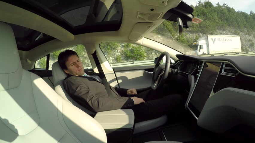 GRAZ, AUSTRIA - FEBRUARY 2nd 2017: Businessman sleeping behind the self-driving steering wheel of an autonomous electric Tesla car. Man fell deeply asleep while driving along the countryside road