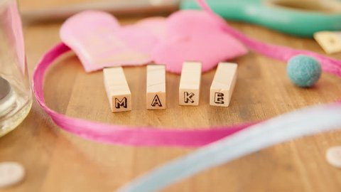 A female hand makes an inspiring message, out of wooden letter blocks, at her wooden craft table, bursting with pretty craft supplies, in her artists' studio. Make!