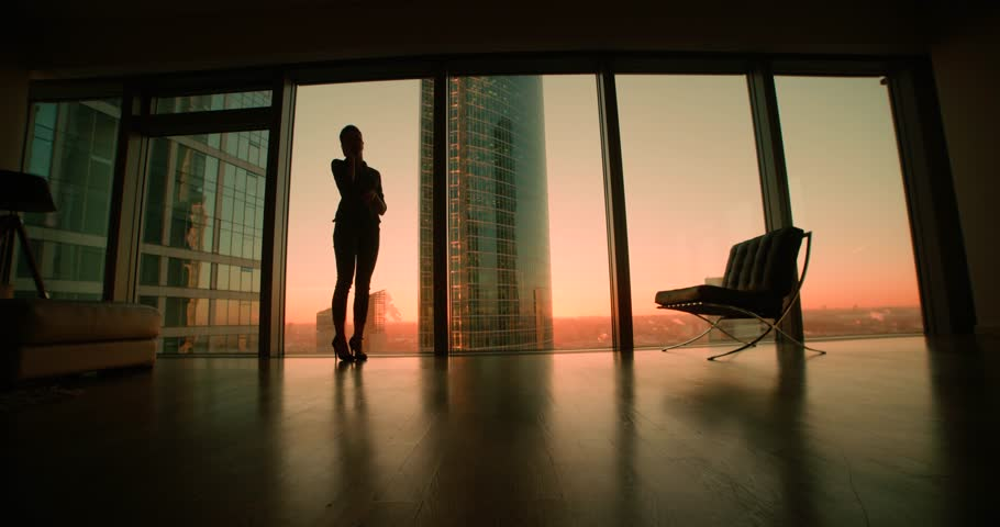 young woman businessman ceo talking on the phone, negotiating the panoramic windows in office skyscraper, sunset, dolly shot