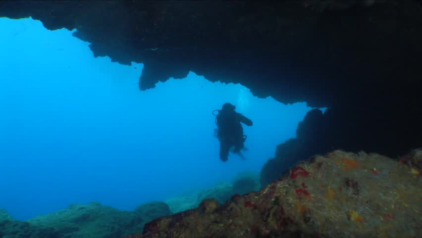 Scuba divers exploring the caves and tunnels and caverns underwater with torch light | Shutterstock HD Video #24429095