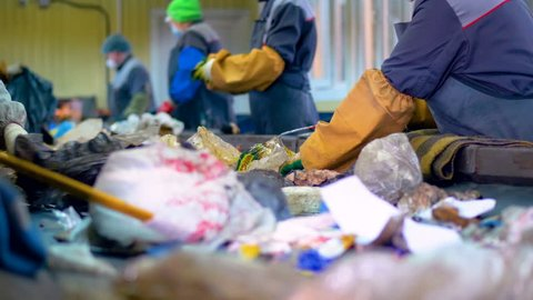 Workers at conveyor sorting garbage at a recycling plant.