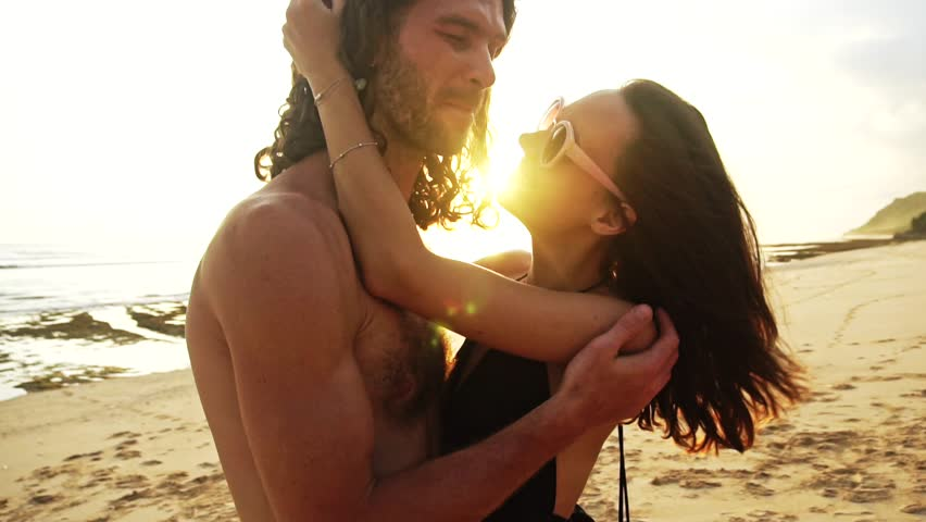 Young happy hipster couple romantically sharing a romantic kiss with the sea in the background at sunset