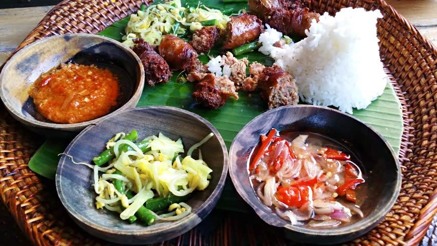 Eating of Urutan Banjar - pork sausage - tradition Balinese dish. 4k video | Shutterstock HD Video #24465905